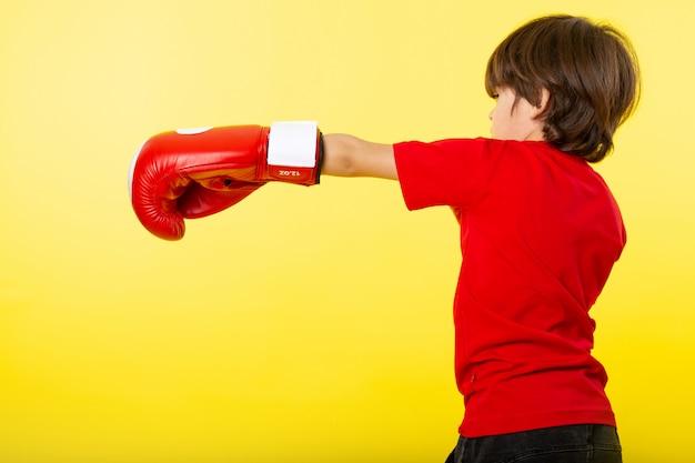 Een vooraanzicht klein kind jongen in rood t-shirt en rode handschoenen op de gele muur