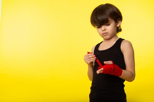 Een vooraanzicht klein kind jongen in zwart t-shirt en gebonden hand met rode weefsel op de gele muur