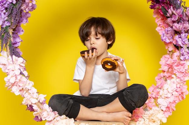 Een vooraanzicht klein kind schattig zoet eten choco donuts op de gele ruimte