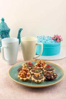 Een vooraanzicht kleine cakes met chocolade en walnoten samen met blauwe verjaardagstaart op het roze bureau
