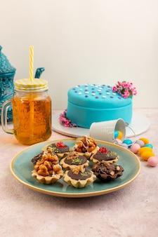 Een vooraanzicht kleine chocoladetaartjes in plaat samen met blauwe verjaardagstaart en drankje op de roze bureau zoete suikercake kleur