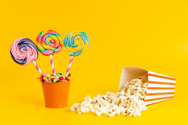 Een vooraanzicht kleurde lollys met kleurrijk suikergoed en popcorn op geel