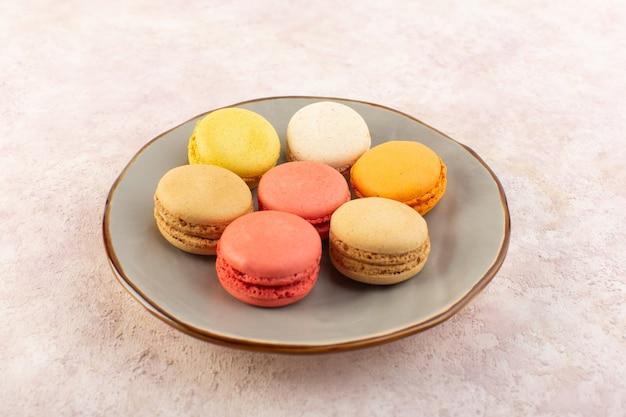 Een vooraanzicht kleurrijke franse macarons in plaat op het roze bureau