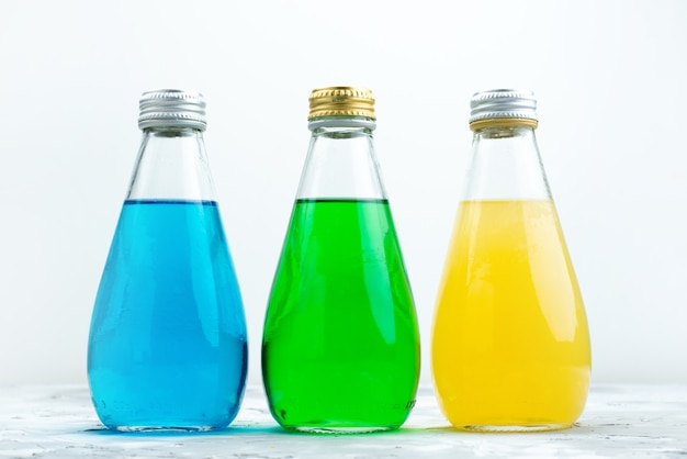 Een vooraanzicht kleurrijke sappen in glazen flessen op wit, sap kleur drinken