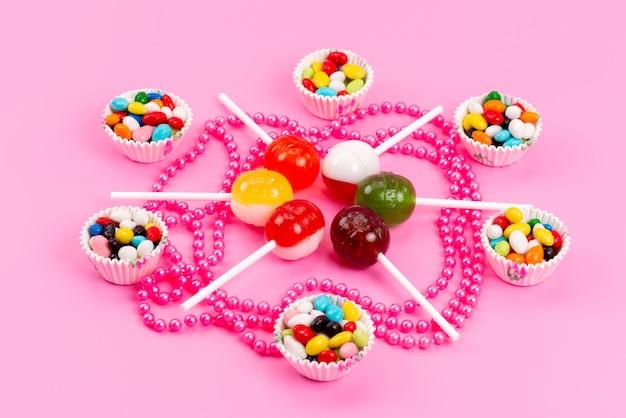 Een vooraanzicht kleurrijke snoepjes samen met lollies geïsoleerd op roze, zoete suikerkleur
