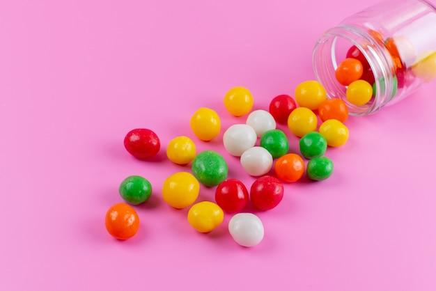 Een vooraanzicht kleurrijke snoepjes zoet en plakkerig op roze, kleur suiker confituur banketbakkerij