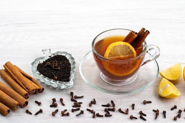 Een vooraanzicht kopje thee met citroen en kaneel op wit, theedessert snoep