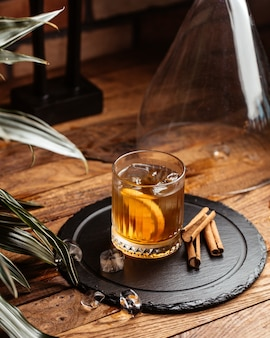 Een vooraanzicht koude alcohol met ijsblokjes op de bruine houten bureaualcohol drinkt wijn