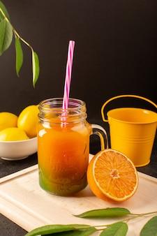 Een vooraanzicht koude cocktail gekleurd binnen glas blikjes met kleurrijke stro citroenen groene bladeren op de houten crème bureau en donker