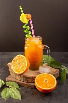 Een vooraanzicht koude cocktail gekleurde binnenkant glas kan met kleurrijke stro met ijsblokjes sinaasappelen en groene bladeren geïsoleerd op het houten bureau en donker