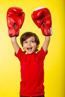 Een vooraanzicht lachende jongen in rode bokshandschoenen en zonder enige hulp