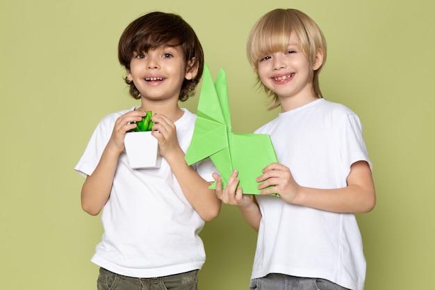 Een vooraanzicht lachende kinderen in witte t-shirts met papieren cijfers en kleine groene plant op de steen gekleurde ruimte