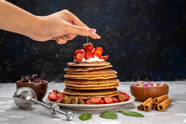 Een vooraanzicht lekkere ronde pannekoeken met room en rode aardbeien op de lichte cake van het bureaufruit