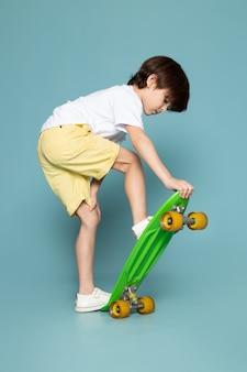 Een vooraanzicht leuke jongen die groen skateboard berijdt op de blauwe ruimte