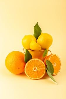Een vooraanzicht mand met citroenen gesneden geheel vers zacht en sappig samen met oranje segment op de crème gekleurde achtergrond