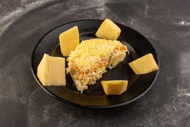 Een vooraanzicht mayyonaised groentesalade met verse kaas binnen zwarte plaat op de grijze het voedselmaaltijd van de lijstsalade