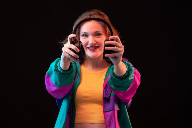 Een vooraanzicht moderne jonge dame in kleurrijke jas oranje t-shirt met zwarte koptelefoon poseren op de zwarte achtergrond dansen moderne mode