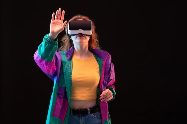 Een vooraanzicht moderne jonge dame in kleurrijke jas oranje t-shirt spelen virtual reality op de zwarte achtergrond gaming interactief spel