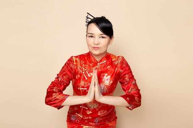 Een vooraanzicht mooie japanse geisha in traditionele rode japanse jurk met haar stokken poseren met haar handen buigen op de crème achtergrond ceremonie onderhoudend oost-japan