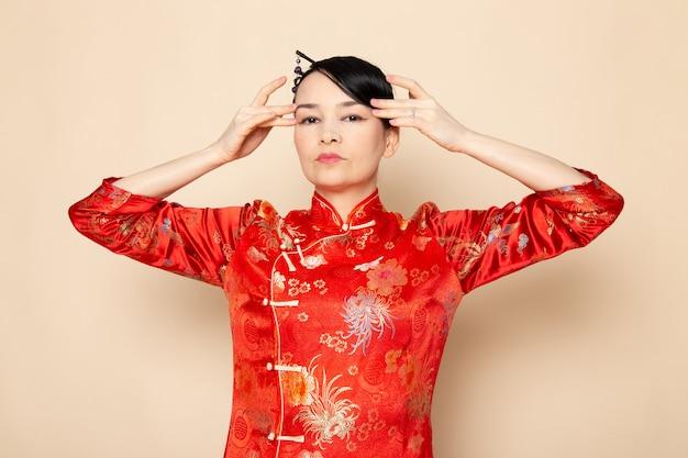 Een vooraanzicht mooie japanse geisha in traditionele rode japanse jurk met haar stokken poseren met haar handen elegant op de crème achtergrond ceremonie onderhoudend oost-japan