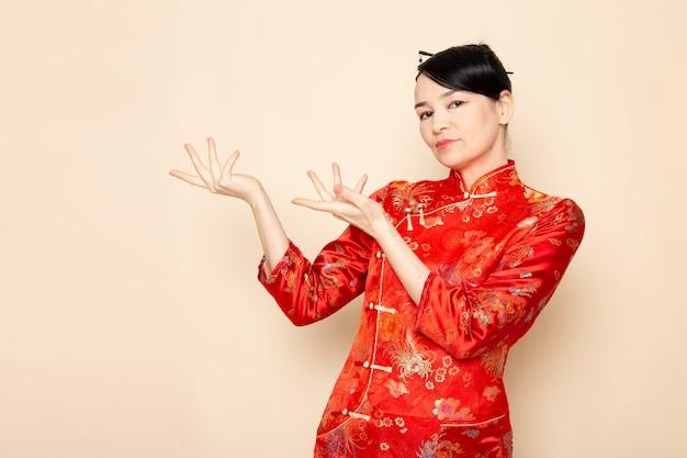 Een vooraanzicht mooie japanse geisha in traditionele rode japanse jurk met haar stokken poseren met haar handen staande op de crème achtergrond ceremonie onderhoudend oosten van japan