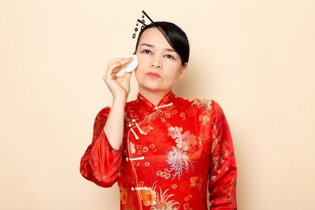 Een vooraanzicht mooie japanse geisha in traditionele rode japanse jurk met haar stokken poseren met weinig witte katoen haar gezicht op de crème achtergrond ceremonie japan schoonmaken