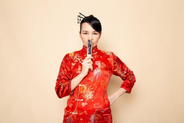 Een vooraanzicht mooie japanse geisha in traditionele rode japanse kleding met haar plakt stellende holdings vouwende ventilator elegant op de room achtergrondceremonie japan