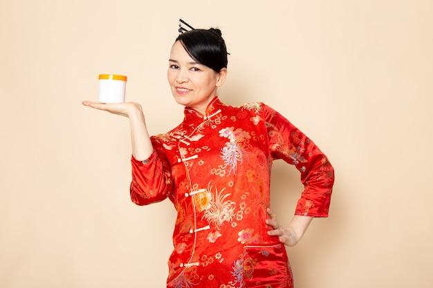 Een vooraanzicht mooie japanse geisha in traditionele rode japanse kleding met haar stokken die holdingscrème stellen kan glimlachend op de room achtergrondceremonie japan