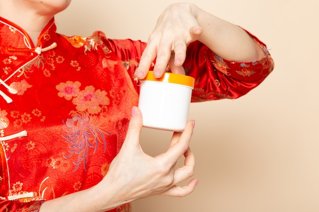 Een vooraanzicht mooie japanse geisha in traditionele rode japanse kleding met haar stokken die holdingscrème stellen kan op de room achtergrondceremonie japan