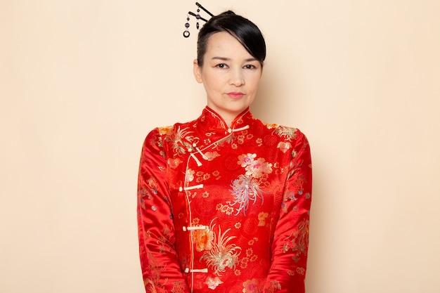 Een vooraanzicht mooie japanse geisha in traditionele rode japanse kleding met haarstokken stellen die zich op de room achtergrondceremonie bevinden die japan onderhouden
