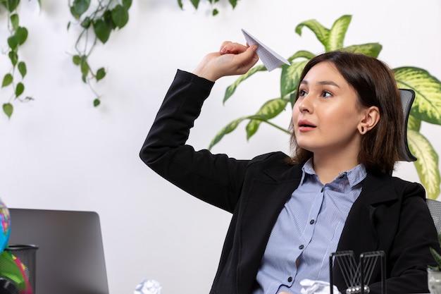 Een vooraanzicht mooie jonge zakenvrouw in zwarte jas en blauw shirt lachend gooien papier vliegtuigen voor tafel zakelijke baan kantoor