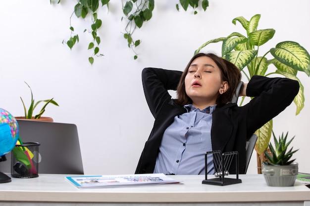 Een vooraanzicht mooie jonge zakenvrouw in zwarte jas en blauw shirt niezen verlangen om te slapen voor tafel zakelijke baan kantoor
