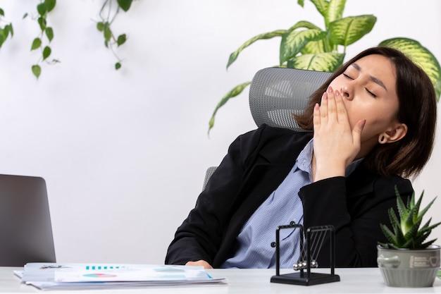 Een vooraanzicht mooie jonge zakenvrouw in zwarte jas en blauw shirt niezen voor tafel zakelijke baan kantoor