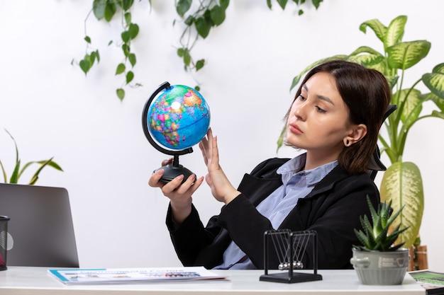 Een vooraanzicht mooie jonge zakenvrouw in zwarte jas en blauw shirt observeren kleine wereldbol voor tafel zakelijke baan kantoor