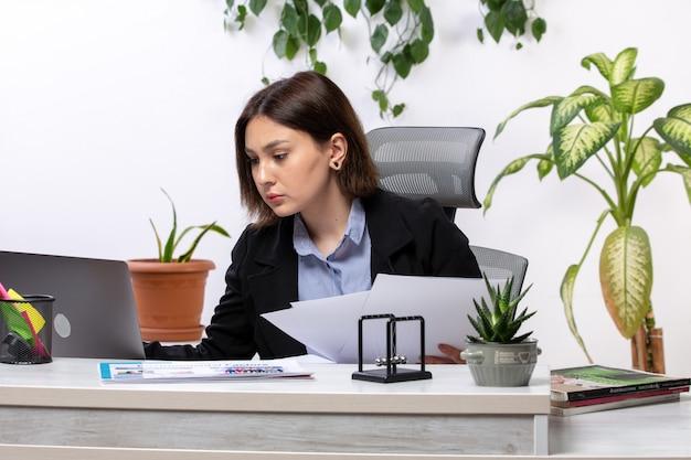 Een vooraanzicht mooie jonge zakenvrouw in zwarte jas en blauw shirt werken met laptop en documenten voor tafel zakelijke baan kantoor