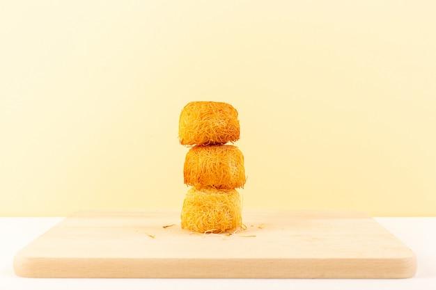 Een vooraanzicht om heerlijke taarten zoete lekkere ronde gevormde bakjes geïsoleerd op de crème gekleurde achtergrond zoete suikerwerk