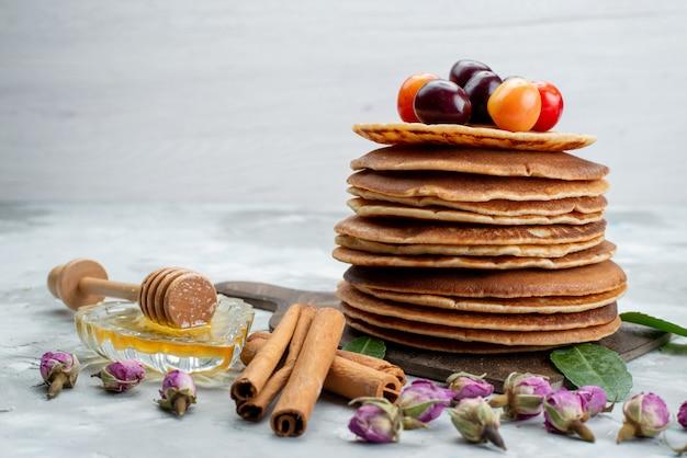 Een vooraanzicht om pannenkoeken gebakken en heerlijk met kersen en kaneel op het lichte fruit van de bureaucake