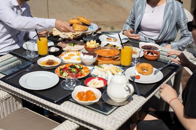 Een vooraanzicht ontbijttafel mensen rond de tafel die hun maaltijd hebben tijdens het ontbijt van de dagmaaltijd