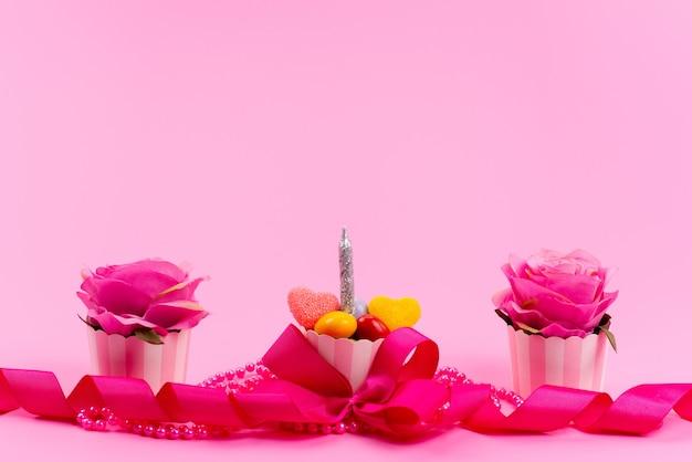 Een vooraanzicht ontworpen roze, presenteert met bloem en kaars op roze, schoonheidskleur aanwezig verjaardag