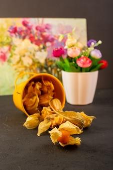 Een vooraanzicht oranje vruchten binnen gele mand ronde vruchten met verf en bloem op grijs