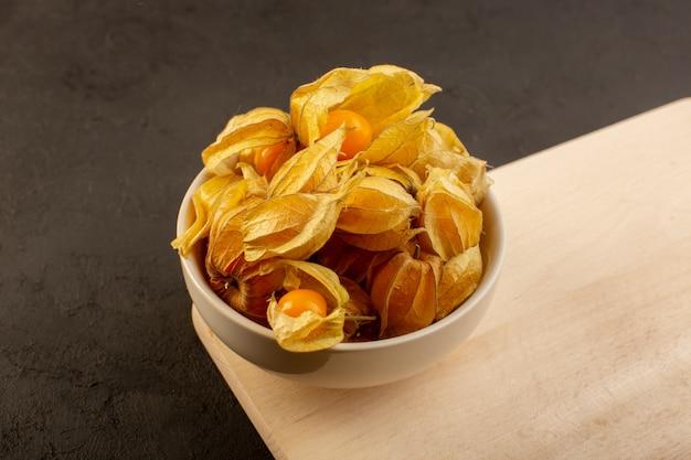 Een vooraanzicht oranje vruchten binnen schillen en witte plaat op houten bureau en donker