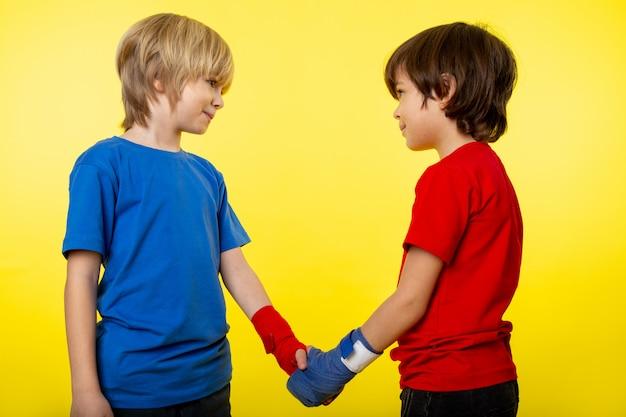 Een vooraanzicht paar jongens die naar elkaar glimlachen, schudden handen in een gekleurd t-shirt en binden hun handen aan de gele muur