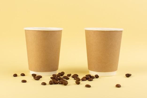 Een vooraanzicht plastic koffiekopjes levering koffiepaar met bruine koffiezaden op het gele oppervlak