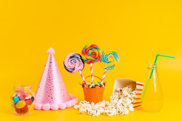 Een vooraanzicht popcorn en lollies met verse cocktail en kleurrijke snoepjes op geel