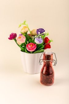 Een vooraanzicht pot met koffie en bloemen op de roze tafelkoffie kleur bloemzaad