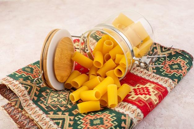 Een vooraanzicht rauwe italiaanse pasta in kleine glazen ketel op kleurrijk tapijt