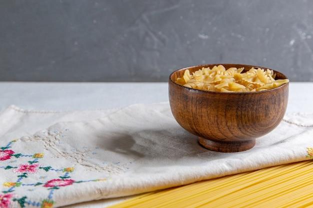 Een vooraanzicht rauwe italiaanse pasta lange en kleine pasta kom