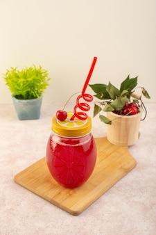 Een vooraanzicht rode kersencocktail met stro op het roze bureau drinkt het fruit van de sapkleur