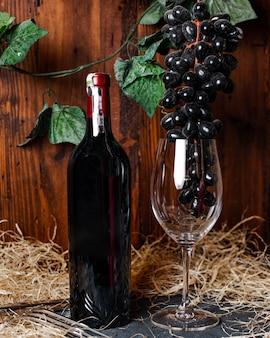 Een vooraanzicht rode wijn zwarte fles rode wijn samen met glas en blauwe druiven alcohol wijnmakerij drinken
