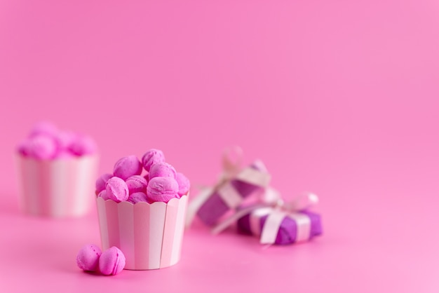 Een vooraanzicht roze, snoepjes samen met paarse geschenkdozen op roze, snoep kleur suiker zoet